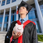Graduated kid holding piggy bank